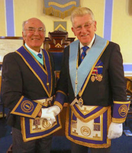 Installing master Sheldon Rawstrone (left) hands over the reins to Martyn Jones.
