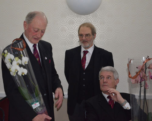 Pictured are Barry (left), and Paul (seated) receiving their orchids from Alan and the companions of Monton Victoria Chapter.