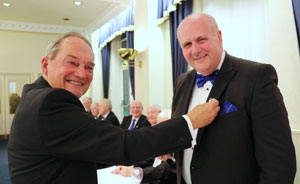 David (right) receives his master's badge of recognition from David Williams.