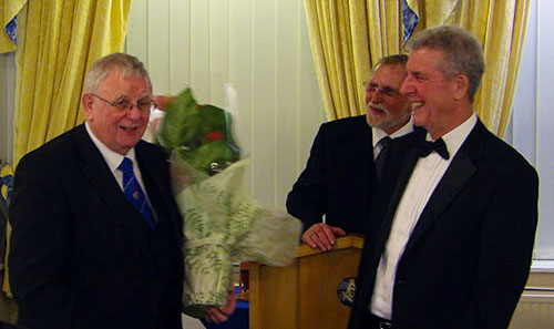 Stewart Seddon (left) receives a bouquet of flowers from Robert Arrand (right) while Brian Ogden ensures that the correct protocol is followed.