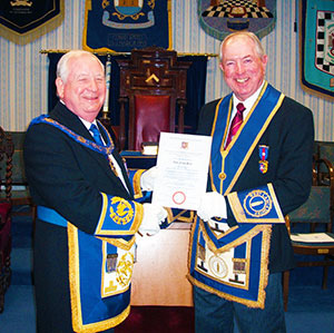 Harry Cox (left) presents Alan Dean with his certificate marking 50 years in the Craft.