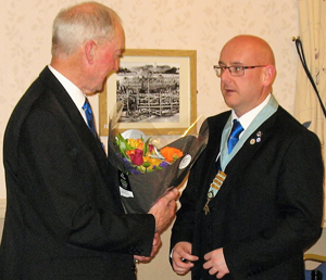 Ian (right) presenting a bouquet to Barry.