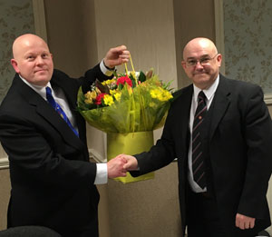 Mark Rollins (right) presents flowers to Malcolm Bell.
