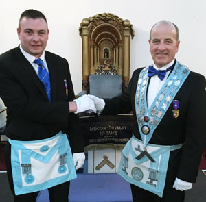 Adam is congratulated by Andrew on his becoming a master Mason.