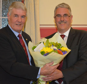 Paul Renton (left) receiving a bouquet of flowers from Andy Barton.