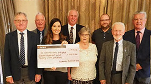 Pictured from left to right, are: Raymond Cookson, Tom Oakes, Hayley Jackson (receiving the cheque for St Catherines Hospice), Ian Heyes, Elizabeth Bridge, Chris Hughes, Eric Nixon and Bryan Hoarty.