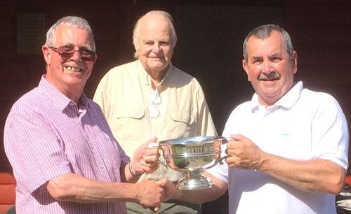 Geoffrey (left) presents the trophy to winner John Bimpson with Len Hart behind.