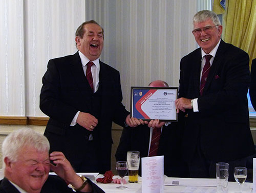Tony Harrison (right) shared a joke with John Turpin (left) and Bob McGown (seated) while displaying the certificate that acknowledges the chapter's Vice Patronage of the MCF 2021 Festival.
