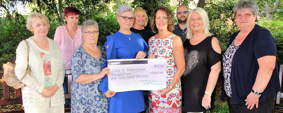Tina Johnstone (fourth from left) receiving a cheque from the Ladies Committee watched on by Chris Hughes (back right).