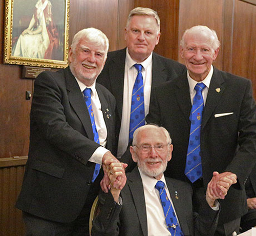 Pictured from left to right standing, are: John Watson, Gowan O'Hagan and Gordon Clarke congratulating Alan (seated) on his achievement.