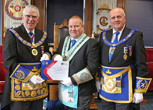Tony (left) presents Phillip with a Vice Patron certificate, watched by David Winder (right).