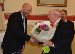 Andrew Pickles (left) presenting a bouquet of flowers to Harry Cox