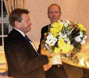 Mark Pedder (right) presents a bouquet to Kevin Poynton for his wife Susan.