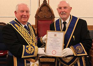 Harry Cox (left) presents Trevor Molloy with his 50 years' service certificate.