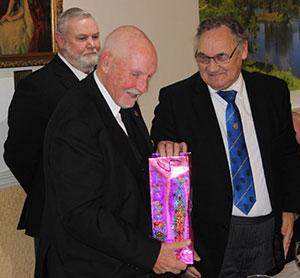 Pictured from left to right, are: Gary Smith, Trevor Molloy (receiving present) and Mike Casey.
