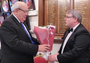 Philip Gunning receives flowers for his wife from Peter Ryan (right).