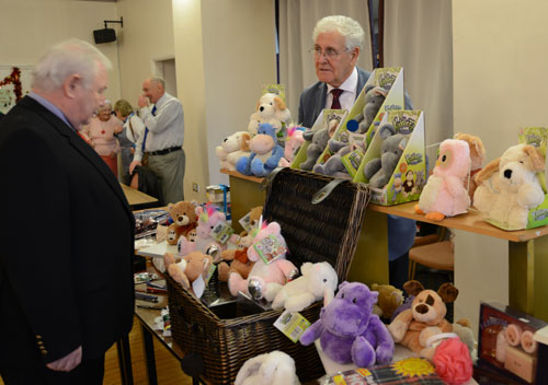 Peter Hegarty, the association secretary buying a microwaveable cuddly soft toy from the stall run by the vice president of the association Malcolm Warren.