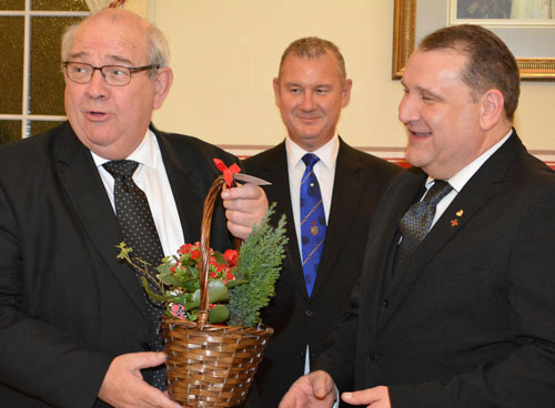 Philip (left) being presented with a flower basket by Darren (right) with Ian (centre) looking on.