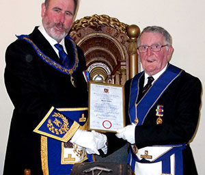 Frank Umbers (left) presenting Bryan Collier with his jubilee certificate.