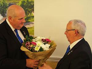 David Winder (left) receives a bouquet of flowers for his wife, Sue.