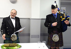 Ted Bottomley addresses the haggis watched keenly by the piper.