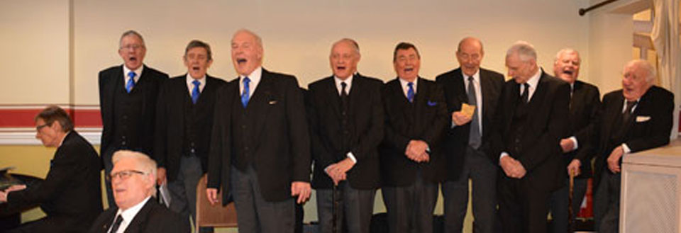 Brethren of the lodge singing 'Welcome to our guests tonight'.