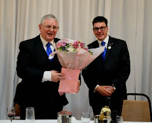 Peter (right) presents Stewart with a flower arrangement for him to take home for his wife.