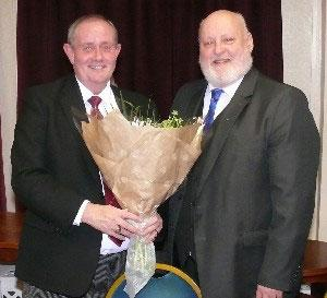 Ian Dawson (right) presents a bouquet of flowers to Tony Hall.
