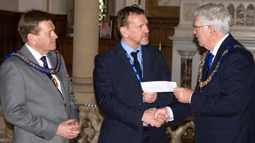 Pictured from left to right Kevin Poynton, John Patterson and presenting the 'Signature Donation', Tony Harrison.
