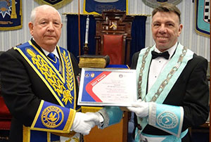 Harry Cox (left) presents Mel Howarth with the MCF 2021 Festival Patron's Certificate.