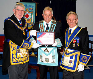 Tony Harrison (left) presenting Eric Moran with the MCF 2021 Festival Patron certificate, with Malcolm Sandywell group charity steward (right).