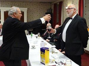 John Darrell (left) toasts David Calvert during the principal's song.