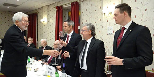 John Chesters (left) toasts Hugh Mett during the principal's song