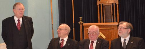 Colin responding with the three principals looking on at the festive board.