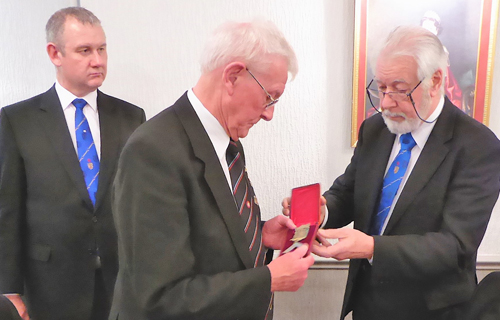 Ray Attwood receives an Apollo Lodge 'Founders Jewel' from Brian Anderson (right)