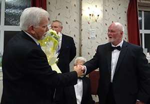David Randerson (left) is presented with flowers by John England.