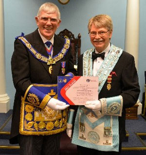 Tony Harrison presents Clive Butterworth (right) with a patronage certificate.