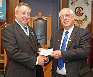 David Parker, (left) presents Alan Howarth with the cheque from the 2019 Preston Masters.
