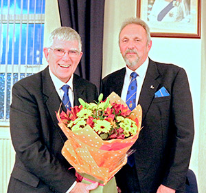 Tony (left) accepts the bouquet from David Asbridge.