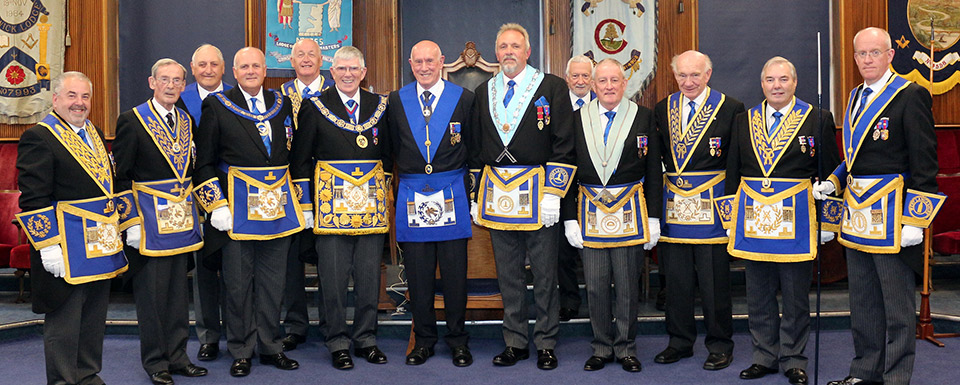 Surrounded by grand officers and flanked by the PrGM and the WM, is Mike Karn (centre).