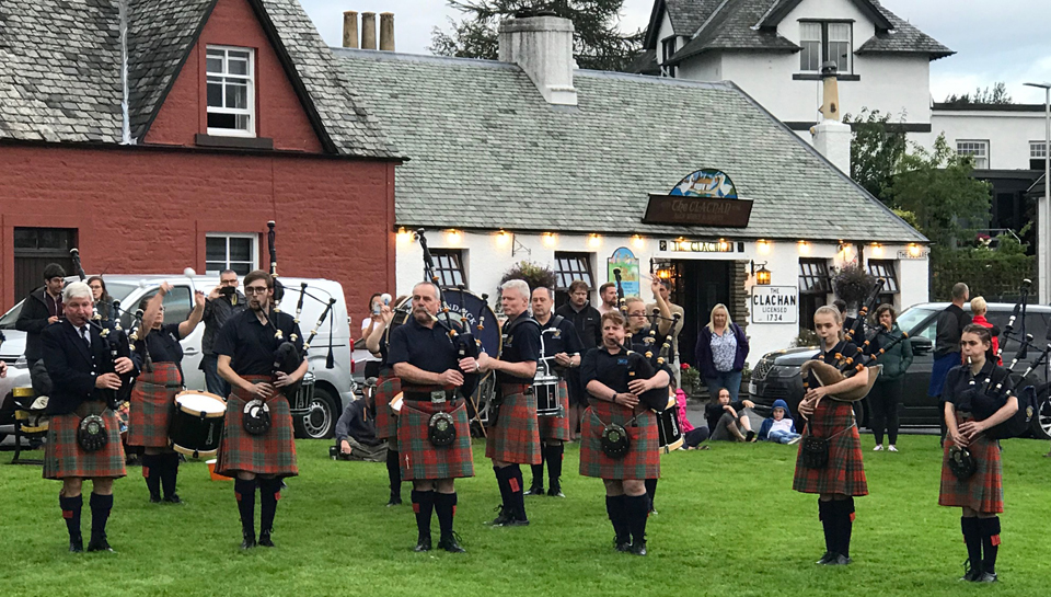 Pipers performing outside the Clachan Inn beside Loch Lomond.