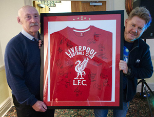 Jim Corcoran (left) presents Mikey Powell with his auction prize.