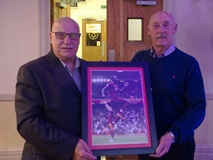 Jim Corcoran (left) presents Rob Jones with his auction prize
