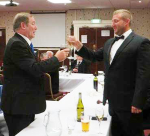 Peter Baldwin (left) toasts Kirk Elliot during the mater's song.