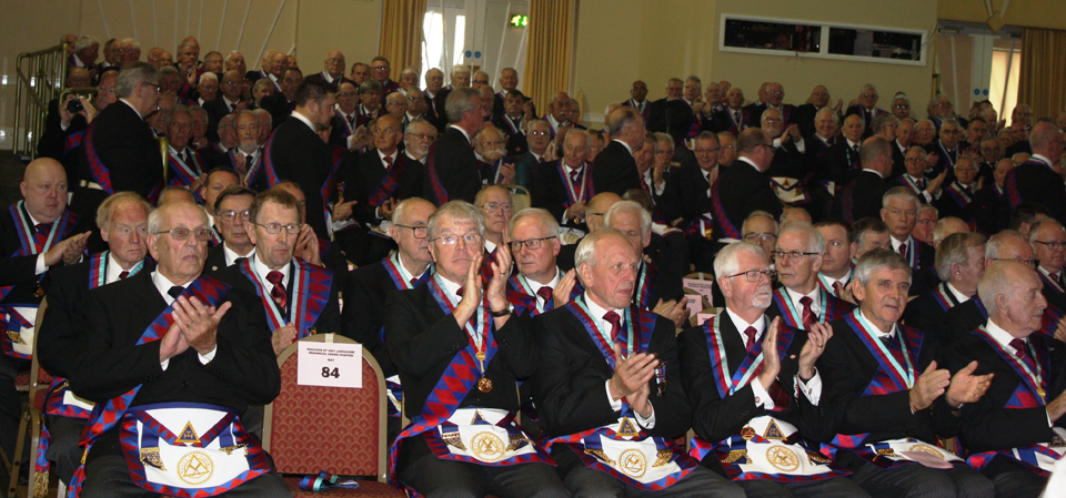 Enthusiastic applause from a packed chapter room as the newly exalted companions enter.