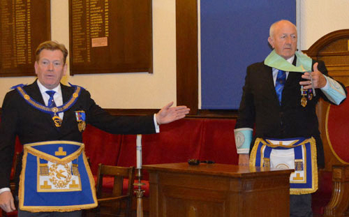 Kevin Poynton (left) demonstrating the junior warden's collar and jewel with Malcolm Myers.