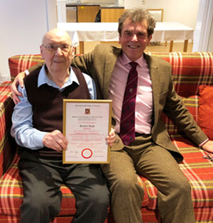 Mike Threlfall (right) sits with Bert and presents his diamond jubilee certificate.