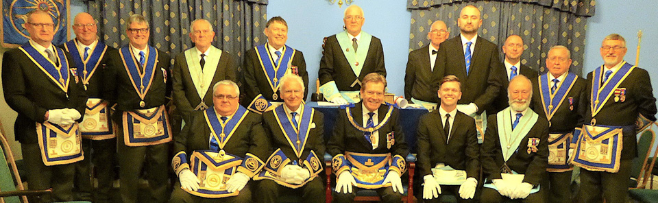 Assistant Provincial Grand Master Kevin Poynton (seated centre) surrounded by brethren of the lodge and visitors, with WM John bell standing back centre.