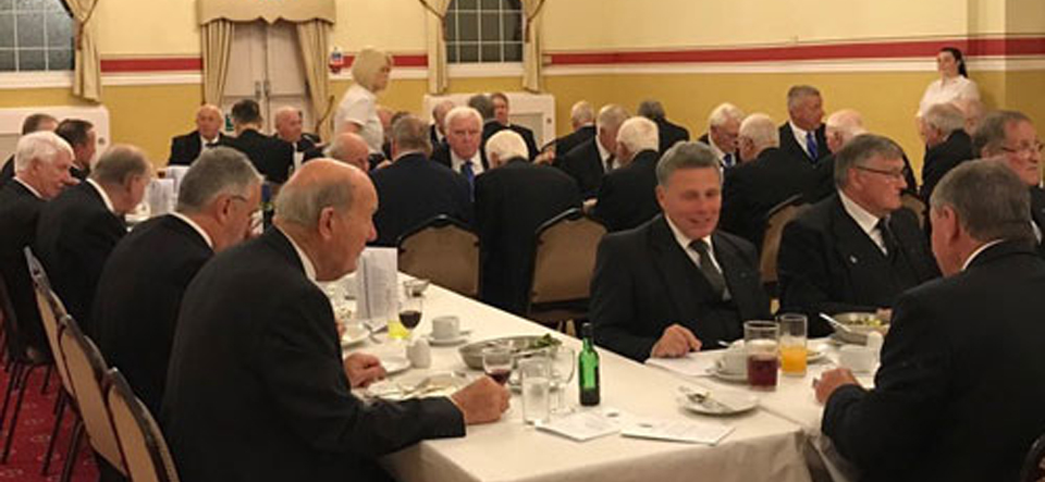 Members and guests enjoying the festive board at Bob Bingham's 50th celebration with Bob on the top table in the foreground.