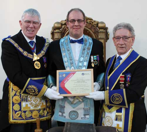 The Provincial Grand Master is pictured presenting Martin Stewart (the lodge WM) with a Grand Patrons certificate, as the group charity steward, Malcolm Sandywell looks on.